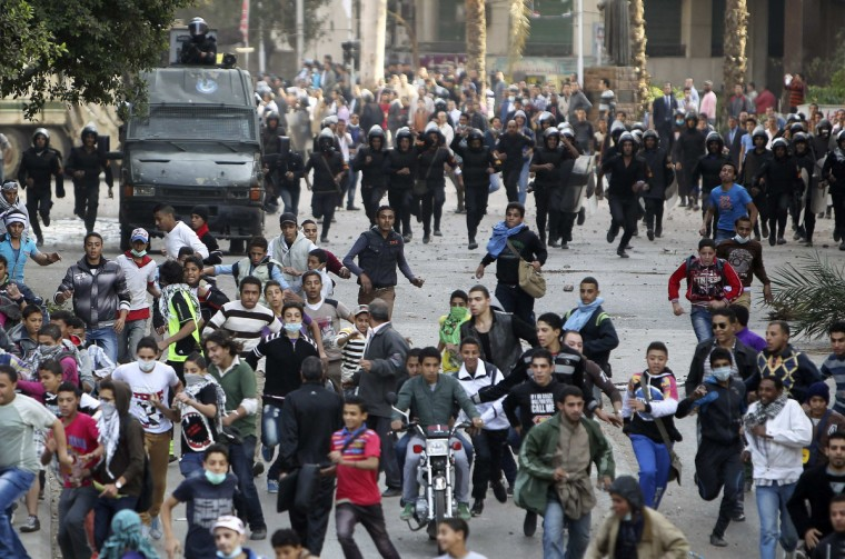 Protesters flee during clashes with police near Tahrir Square in Cairo. Hundreds of demonstrators were in Cairo's Tahrir Square for a sixth day on Wednesday, demanding that President Mohamed Mursi rescind a decree they say gives him dictatorial powers, while two of Egypt's top courts stopped work in protest. (Asmaa Waguih/Reuters)