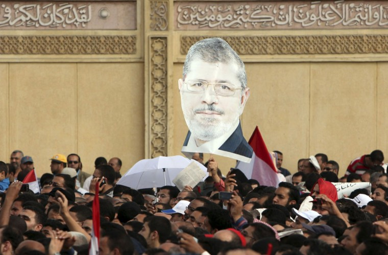 Supporters of Egyptian President Mohamed Mursi chant pro-Mursi slogans and carried an image of Mursi, during a protest praising a new decree he issued on Thursday, in front of the presidential palace in Cairo November 23 , 2012. (Asmaa Waguih/Reuters)