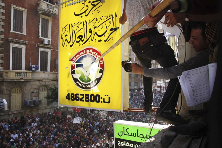 Protesters attack the logo of the Muslim Brotherhood's Freedom and Justice Party after ransacking the party's office in Alexandria November 23, 2012. (Stringer/Reuters)