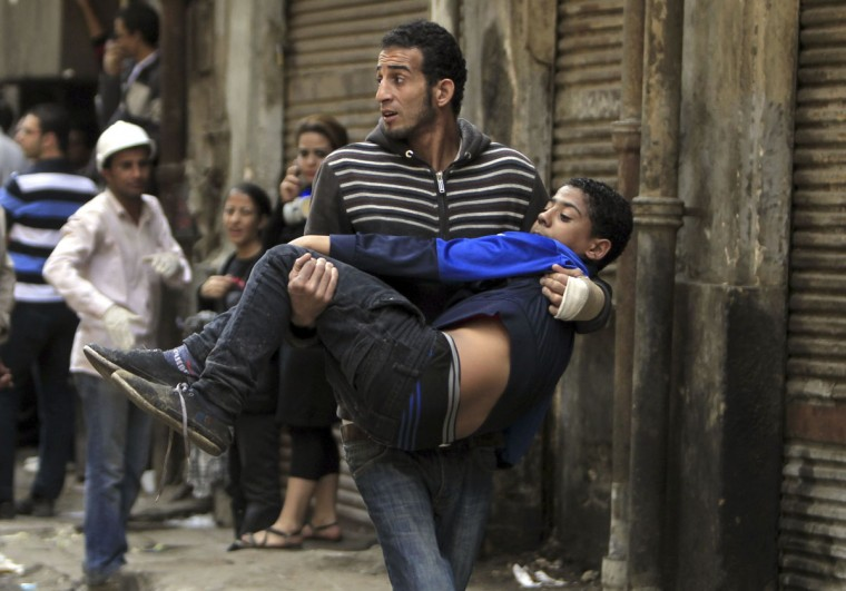 A protester carries an injured fellow protester during clashes with the police at Tahrir square in Cairo November 23, 2012. (Mohamed Abd/Reuters)