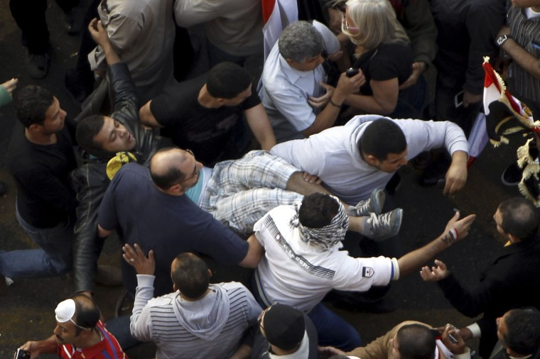 Protesters carry an injured fellow protester during clashes with the police at Tahrir square in Cairo November 23, 2012. (Mohamed Abd El Ghany/Reuters)