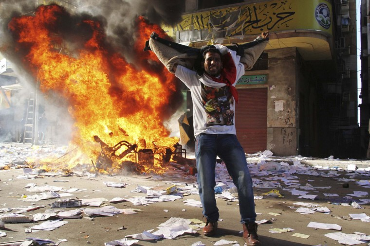 A protester cheers as items ransacked from an office of the Muslim Brotherhood's Freedom and Justice Party burn in Alexandria November 23, 2012. (Stringer/Reuters)