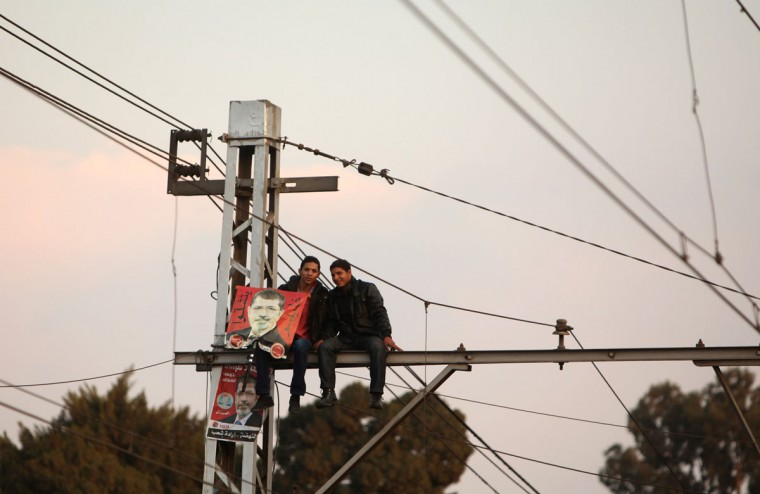 Supporters of Egypt's President Mohamed Mursi sit on electric poles as they watch him speak in front of the presidential palace in Cairo November 23, 2012. (Asmaa Waguih/Reuters)