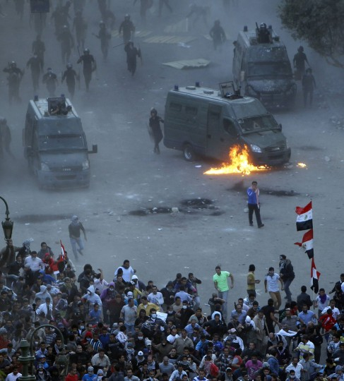 Flames burn around a police vehicle after protesters threw a molotov cocktail at it during clashes at Tahrir square in Cairo November 23, 2012. (Mohamed Abd El Ghany/Reuters)