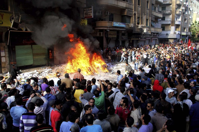 People watch as protesters burn items ransacked from an office of the Muslim Brotherhood's Freedom and Justice Party in Alexandria November 23, 2012. (Stringer/Reuters)