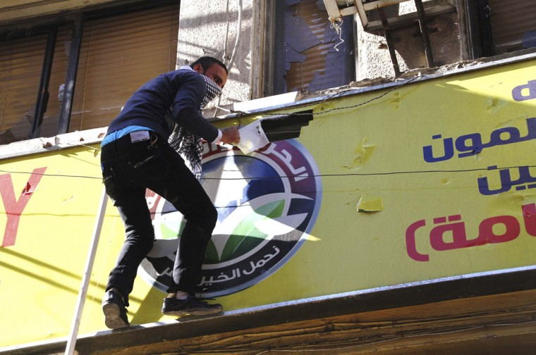 A protester destroys the logo of the Muslim Brotherhood's Freedom and Justice Party after ransacking the party's office in Alexandria November 23, 2012. (Stringer/Reuters)