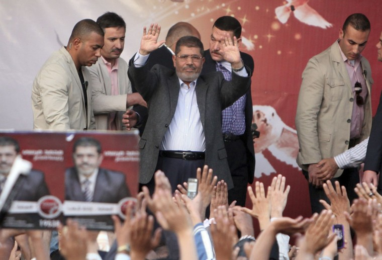 Egypt's President Mohamed Mursi (C) waves after speaking to supporters in front of the presidential palace in Cairo November 23, 2012. (Asmaa Waguih/Reuters)