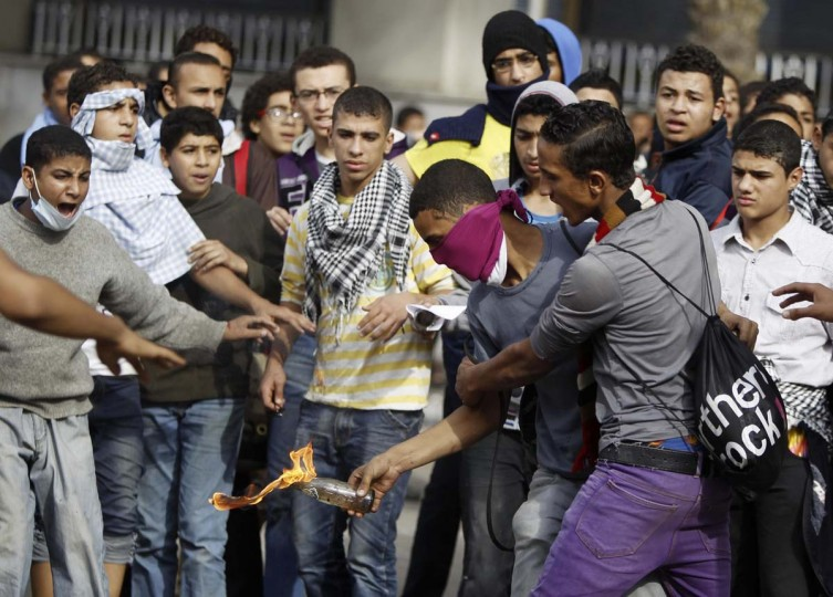 A youth tries to stop an anti-Mursi protester from throwing a petrol bomb at riot police along a road which leads to the U.S. embassy, near Tahrir Square in Cairo. The body writing Egypt's new constitution began a session to vote on a final draft on Thursday, a move President Mohamed Mursi's allies in the Muslim Brotherhood hope will help end a crisis prompted by a decree expanding his powers. (Amr Abdallah Dalsh/Reuters photo)