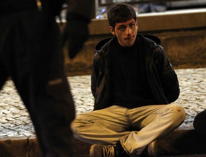 An injured protester sits in the street after being detained during clashes at a 24-hour nationwide general strike in Lisbon. Spanish and Portuguese workers will stage the first coordinated general strike across the Iberian Peninsula on Wednesday, shutting transport, grounding flights and closing schools to protest against spending cuts and tax hikes. (Rafael Marchante/Reuters)
