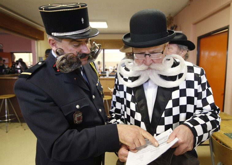 Participants read documents as they take part in the 2012 European Beard and Moustache Championships in Wittersdorf near Mulhouse, Eastern France, September 22, 2012. (Vincent Kessler/Reuters)