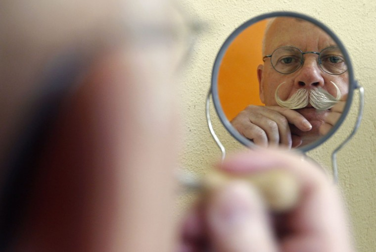 A participant is reflected on a mirror as he gets ready for the 2012 European Beard and Moustache Championships in Wittersdorf near Mulhouse, Eastern France, September 22, 2012. More than a hundred participants competed in the first European Beard and Moustache Championships organized in France. (Vincent Kessler/Reuters)