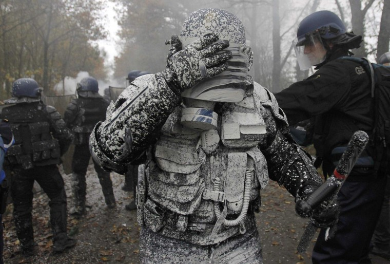 A French riot gendarme reacts after being covered with lime during clashes with demonstrators during an evacuation operation on land that will become the new airport in Notre-Dame-des-Landes, western France. The new airport, some 30km (19 miles) from Nantes, is scheduled to be constructed for 2017. (Stephane Mahe/Reuters)