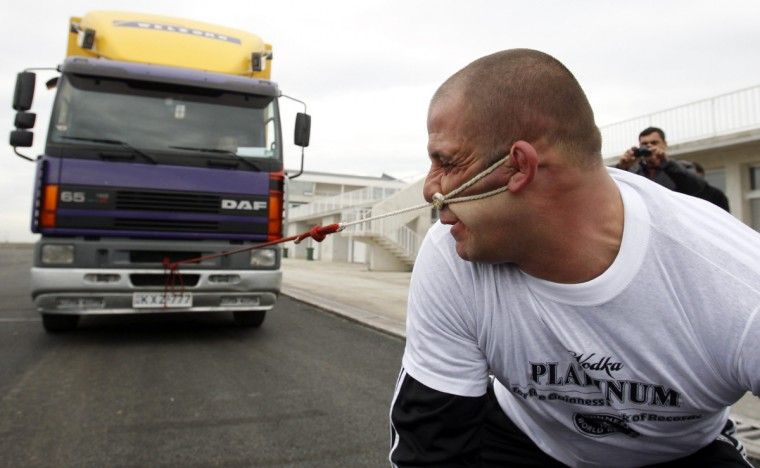 Lasha Pataraia pulls an eight-ton truck with his ear during a test event in Rustavi outside Tbilisi. The 32-year-old sportsman will attempt to break a record registered by the Guinness Book of World Records by the end of the month, according to organisers. (David Mdzinarishvili /Reuters)