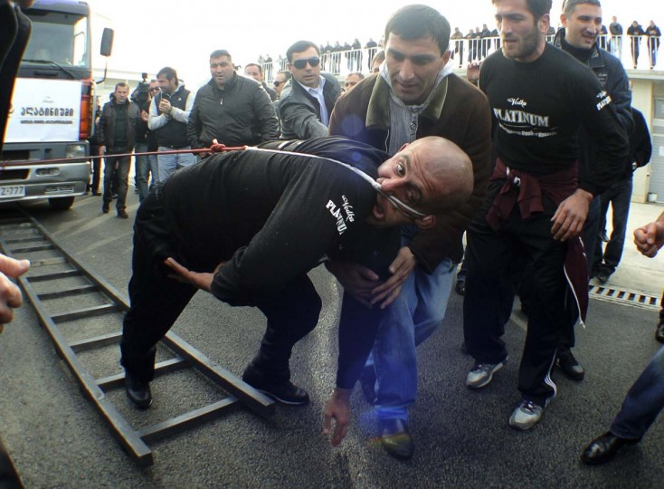Lasha Pataraia pulls a truck, which weighs 8,250kg (8 tons), with his ear during an event to break the Guinness Book of World Records in Rustavi, outside Tbilisi. The 32-year-old broke a Guinness record after he managed to pull the truck with his ear for 21,50 metres (70.5 feet), according to organisers. (Irakli Gedenidze/Reuters photo)