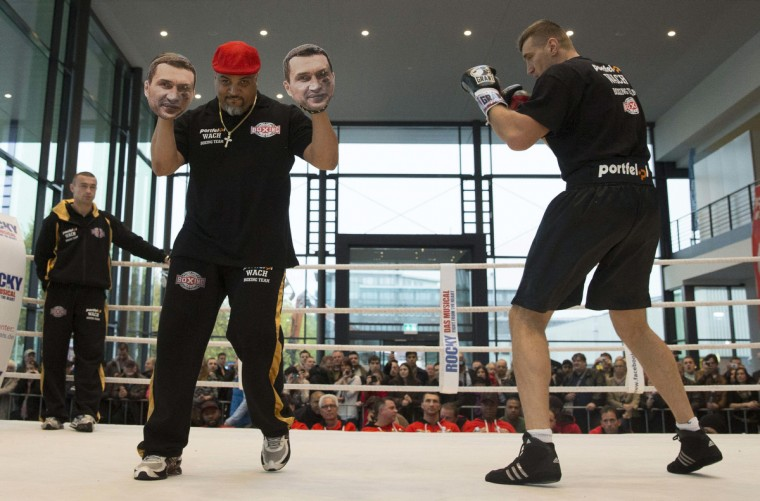 Juan De Leon (L) the coach of Polish boxing contender Mariusz Wach (R) holds up sparring gloves with images of opponent Vladimir Klitschko, as they joke during a public training session in Hamburg. Ukrainian WBO, IBO and IBF heavy weight boxing world champion Vladimir Klitschko will fight Wach in a title bout on November 10 at the O2 World in Hamburg. (Morris Mac Matzen/Reuters)