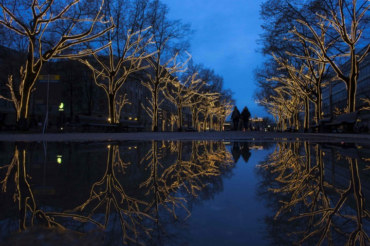 Trees decorated with Christmas lights are reflected in a puddle as people walk along the Unter den Linden promenade in Berlin. (Thomas Peter/Reuters)