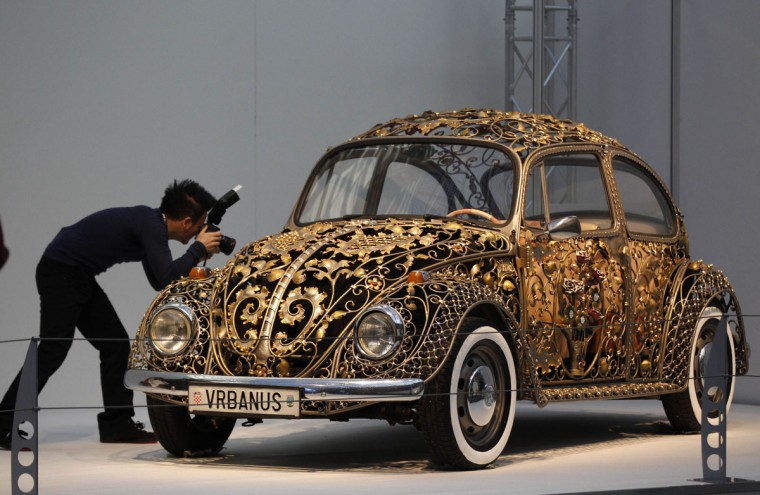 A visitor takes a picture at a modified Volkswagen VW Beetle during a press presentation prior to the Essen Motor Show in Essen. About 600 exhibitors will present their latest developments at the Essen trade fair from December 1 until December 9, 2012. (Ina Fassbender/Reuters)