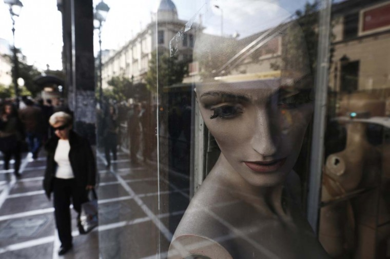 "A woman walks past mannequins in a closed shop at central Athens. Thousands of small shops and businesses have closed up over the past few years of Europe's economic downturn, especially in the so-called ""PIIGS"" countries of Portugal, Italy, Ireland, Greece and Spain. (John Kolesidis/Reuters photo)"