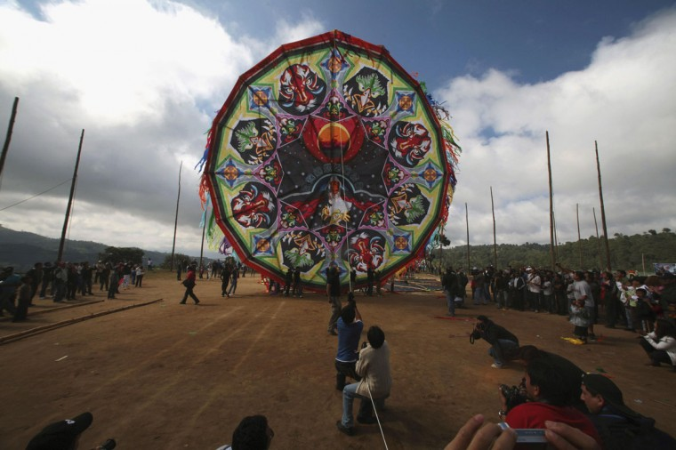 Men lift up a giant kite into the sky to celebrate the Day of the Dead at a cemetery in Santiago Sacatepequez, about 40 km (25 miles) from Guatemala City, November 1, 2012. (William Gularte/Reuters)