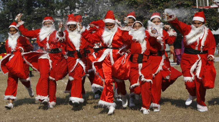 Students dressed in Santa Claus costumes perform as part of their Christmas celebrations in their school in the northern Indian city of Chandigarh on December 20, 2011. (Ajay Verma/Reuters)