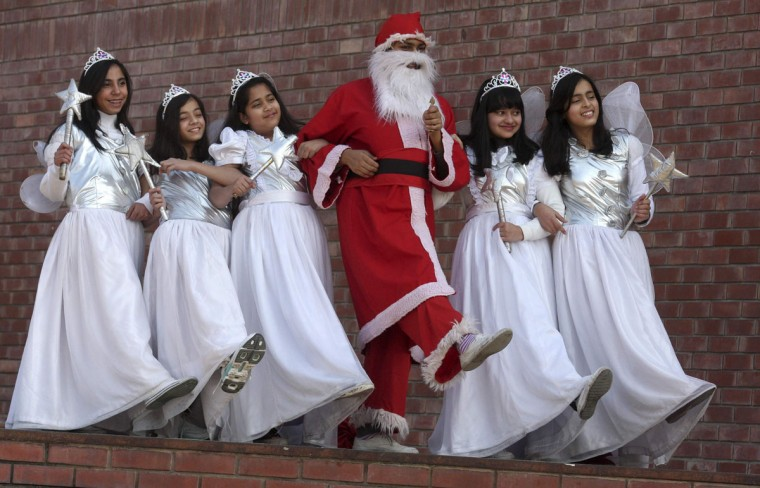 A student dressed up as Santa Claus dances with other students during a Christmas celebration at a school in the northern Indian city of Chandigarh December 23, 2010. (Ajay Verma/Reuters)