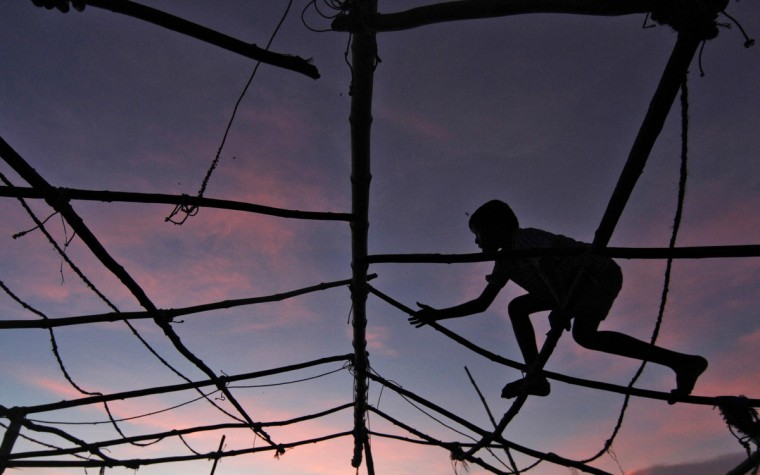 A boy is silhouetted against the setting sunlight as he plays over a damaged hut at Marina beach in the southern Indian city of Chennai. (Babu/Reuters)