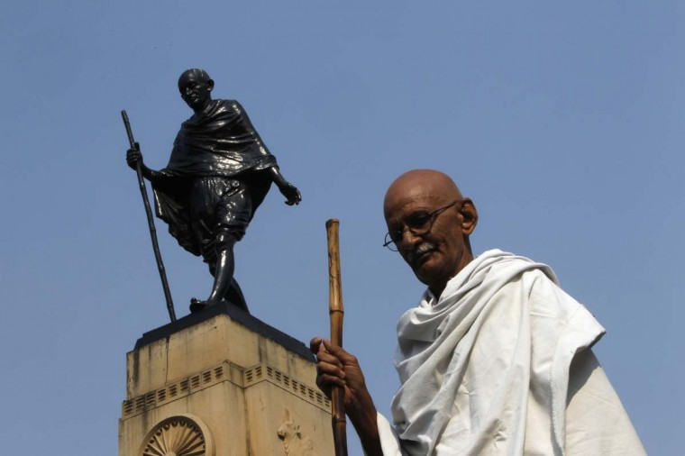 Mahesh Chaturvedi, 63, who dresses up like Mahatma Gandhi, poses for a photo in front of a statue of Gandhi in the old quarters of New Delhi October 25, 2012. (Mansi Thapliyal/Reuters)