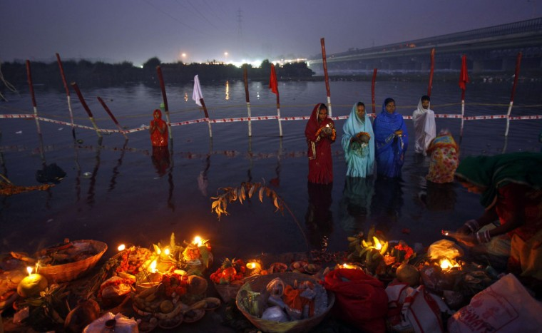Hindu devotees stand in the waters of river Yamuna to offer prayers to the Sun god during the Hindu religious festival 'Chhat Puja' at dawn in New Delhi. Hindu devotees worship the Sun god and fast all day for the betterment of their family and society during the festival. (Mansi Thapliyal/Reuters)