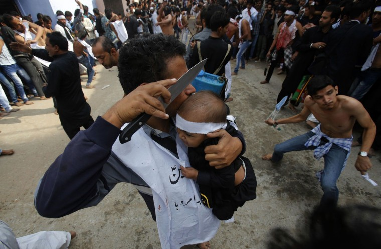 A Shi'ite Muslim man uses a knife to gash a child's head during a Muharram procession ahead of Ashura in Amroha, in the northern Indian state of Uttar Pradesh. Ashura is a 10-day-long event where Shi'ite Muslims commemorate the death of Prophet Mohammad's grandson Imam Hussein in battle in 680AD. (Adnan Abidi/Reuters)