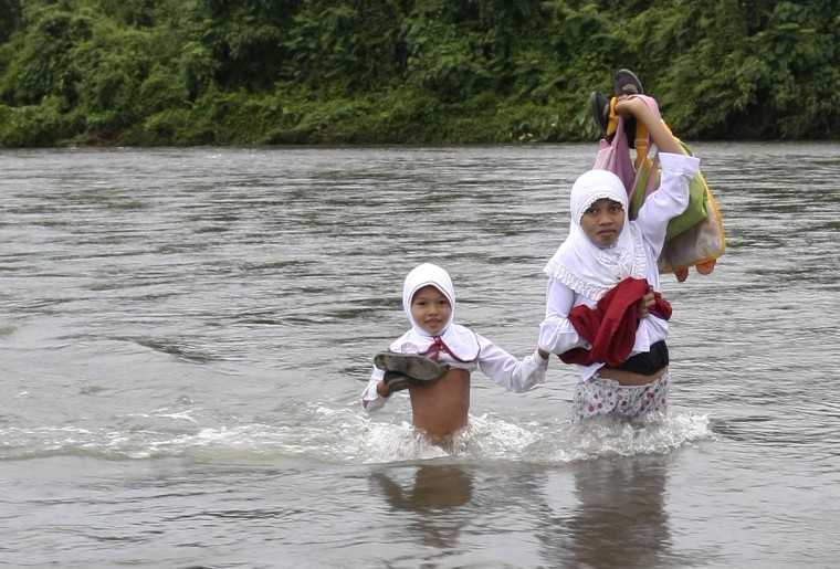 Elementary school girls cross a river to go to school in the village of Nagari Koto Nan Tigo in Indonesia's West Sumatra province. School children from around 46 families in the village are forced to cross the river every day because there is no bridge, villagers said. (Reuters)