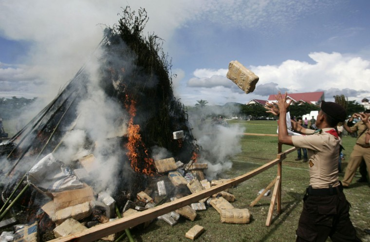 October 17, 2012: A high school student and local officials throw bundles of marijuana into a fire at the police headquarters in Banda Aceh, Indonesia. Police destroyed about 5.1 tons of marijuana after they were seized in raids during recent months in several Aceh areas, a police officer said on Wednesday. (Junaidi Hanafiah/Reuters)