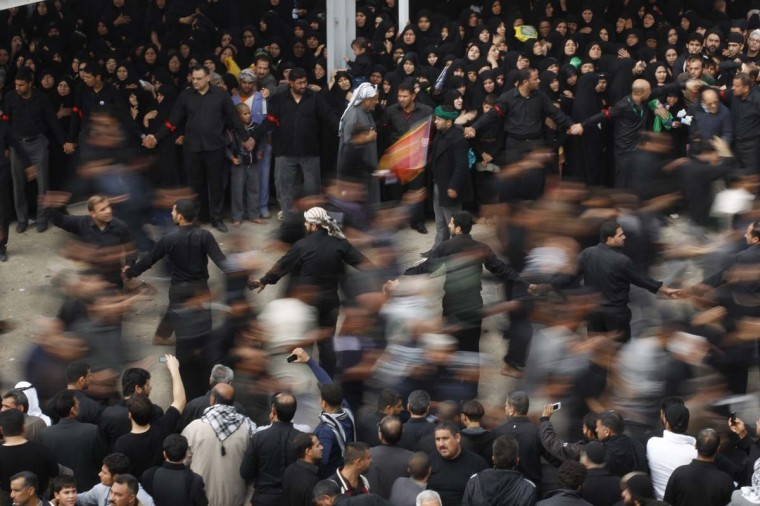Shi'ite pilgrims run between the Imam Hussein and Imam Abbas shrines as part of a ritual of the Ashura ceremony in Karbala, 50 miles southwest of Baghdad, November 25, 2012. The festival, commemorated by Shi'ite Muslims, marks the martyrdom of the Prophet Mohammad's grandson Hussein. (Mohammed Ameen/Reuters)