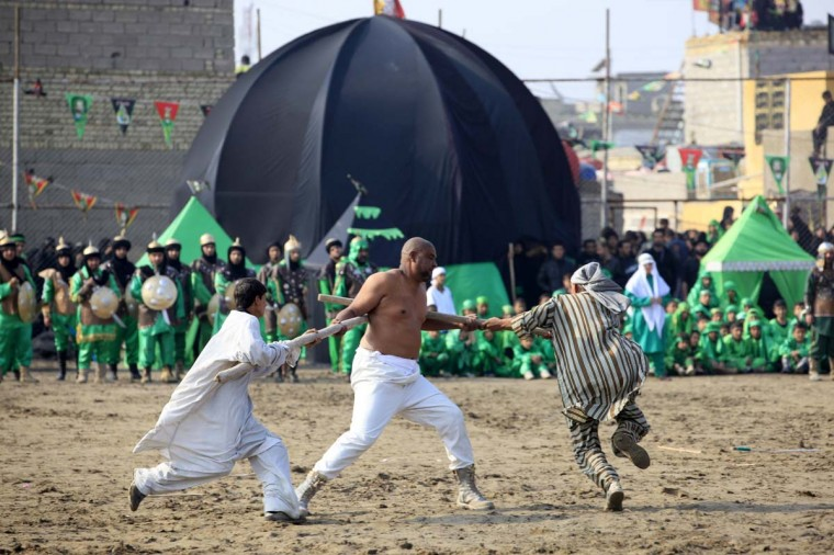 Local actors dressed as ancient warriors re-enact a scene from the 7th century battle of Kerbala during the Shi'ite religious festival of Ashura in Baghdad's Sadr City November 25, 2012. (Thaier Al-Sudani/Reuters)