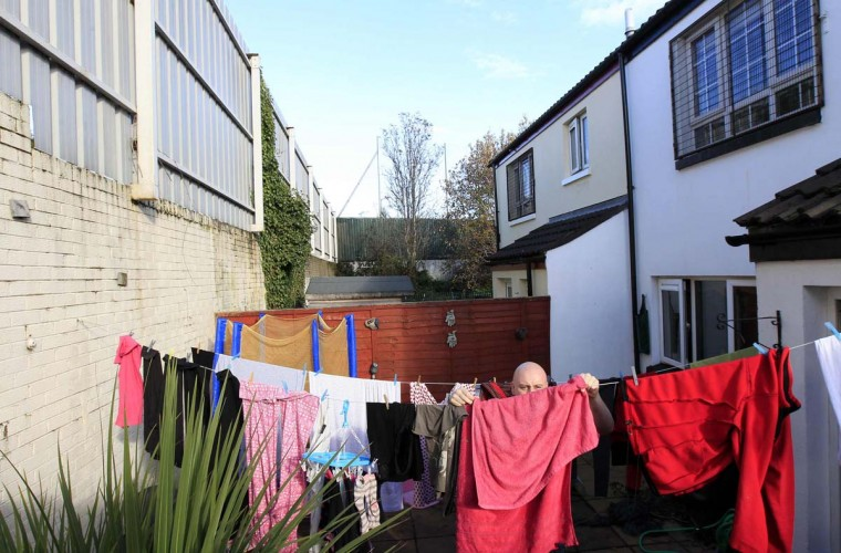 "Stephen McGarry, hangs out the laundry in the back garden of his home on Clonard Street in west Belfast. When asked would he like to see the peace wall that divides Catholic and Protestant communities taken down, McGarry replied, ""It never should be taken down. But mum would love to see holes in it to let the light through."" The first barriers were built in 1969, following the outbreak of the Northern Ireland riots known as ""The Troubles."" They were built as temporary structures meant to last only six months, but they have multiplied over the years, from 18 in the early 1990s to 40 today; in total they stretch over 13 miles (21 km), with most located in Belfast. (Cathal McNaughton/Reuters photo)"