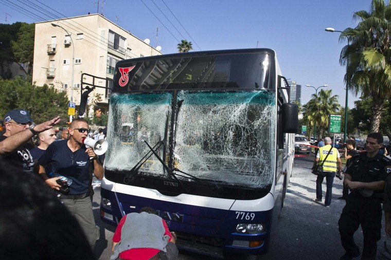 NOVEMBER 21: Israeli police officers stand around a damaged bus at the scene of an explosion in Tel Aviv. A bomb exploded on the bus in central Tel Aviv on Wednesday, wounding 15 people in what Israeli officials said was a terrorist attack that could complicate efforts to secure a ceasefire in the Gaza Strip. (Baz Ratner/Reuters)