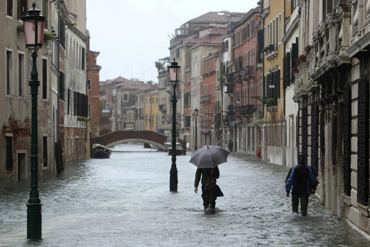 People walk in a flooded street during a period of seasonal high water in Venice on Nov. 11, 2012. The water level in the canal city rose to 149 cm (59 inches) above normal, according to a local monitoring institute. (Manuel Silvestri/Reuters)