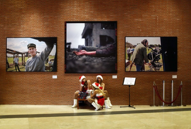 Girls dressed as Santarinas rest under the Full Metal Jacket Diary Redux photo exhibition by U.S.actor Matthew Modine at the Rome Film Festival in Rome. (Alessandro Bianchi/Reuters)