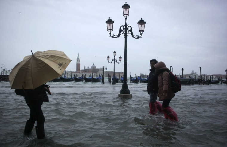 People walk through a flooded street during a period of seasonal high water in Venice on Nov. 11, 2012. The water level in the canal city rose to 149 cm (59 inches) above normal, according to a local monitoring institute. (Manuel Silvestri/Reuters)