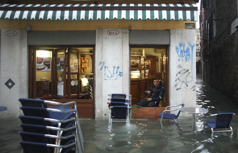 A man rests in a shop in a flooded street during a period of seasonal high water in Venice on Nov. 11, 2012. The water level in the canal city rose to 149 cm (59 inches) above normal, according to a local monitoring institute. (Manuel Silvestri/Reuters)