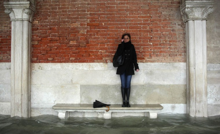 A woman stands on a bench above a flooded street during a period of seasonal high water in Venice on Nov. 11, 2012. High tides combined with rains and wind that struck the city in northern Italy, with flooding reaching about 150 centimeters (roughly 59 inches). (Manuel Silvestri/Reuters)