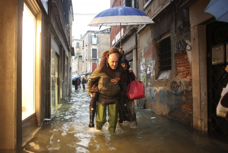People walk in a flooded street during a period of seasonal high water in Venice on Nov. 11, 2012. High tides combined with rains and wind that struck the city in northern Italy, with flooding reaching about 150 centimeters (roughly 59 inches). (Manuel Silvestri/Reuters)