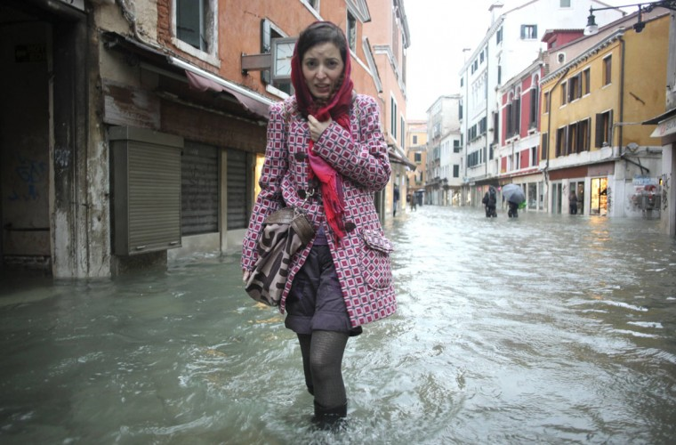 "A woman walks in a flooded street during an ""acqua alta"" (literally, ""high water"") in Venice on Nov. 11, 2012. Rain and wind struck the city in northern Italy, with flooding reaching about 150 centimeters (roughly 59 inches) in Venice. (Manuel Silvestri/Reuters)"