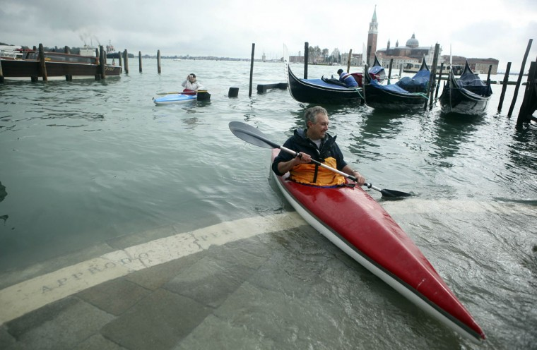 A man rows a kayak in front of a flooded St. Mark's Square during a period of seasonal high water in Venice on Nov. 1, 2012. The water level in the canal city rose to 140 cm, about 55 inches, above normal, according to a monitoring institute. (Manuel Silvestri/Reuters)