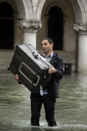 A man carries his luggage through the flooded St. Mark Square during a period of seasonal high water in Venice on Nov. 1, 2012. The water level in the canal city rose to 140 cm, about 55 inches, above normal, according to a monitoring institute. (Manuel Silvestri/Reuters)