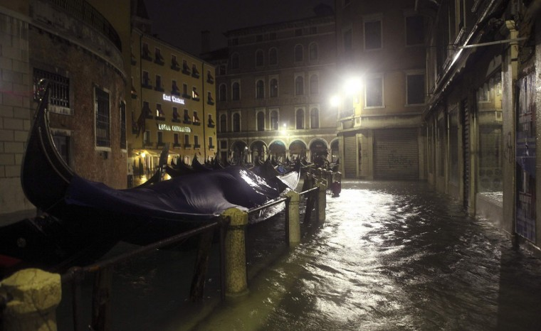 Unused gondolas are pictured near a flooded St. Mark's Square at night during a period of seasonal high water in Venice on Nov. 1, 2012. The water level in the canal city rose to 140 cm, about 55 inches, above normal, according to a monitoring institute. (Manuel Silvestri/Reuters)