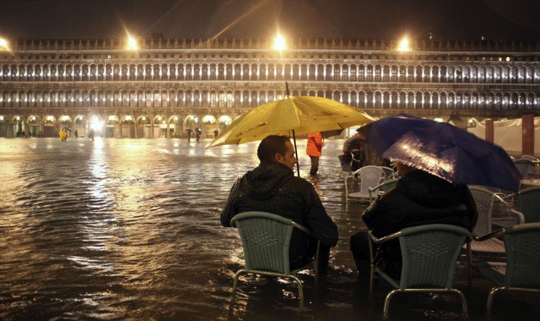 People sit on chairs in a flooded St Mark's Square at night during a period of seasonal high water in Venice on Nov. 1, 2012. The water level in the canal city rose to 140 cm, about 55 inches, above normal, according to a monitoring institute. (Manuel Silvestri/Reuters)