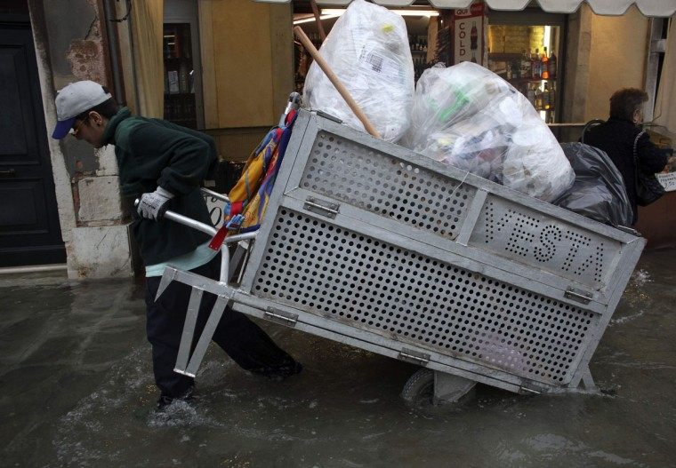 A worker pulls a garbage cart during a period of seasonal high water in Venice on Oct. 27, 2012. The water in the canal city rose to 127 centimeters, or 50 inches, above the normal level. (Manuel Silvestri/Reuters)