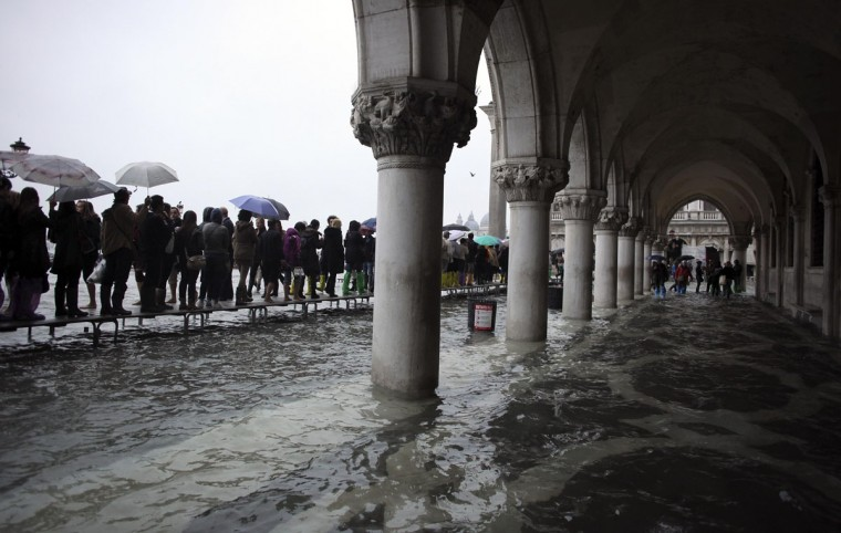 Tourists walk on raised platforms on top of floodwaters in St. Mark Square during a period of seasonal high water in Venice on Oct. 27, 2012. The water in the canal city rose to 127 centimeters, or 50 inches, above the normal level. (Manuel Silvestri/Reuters)
