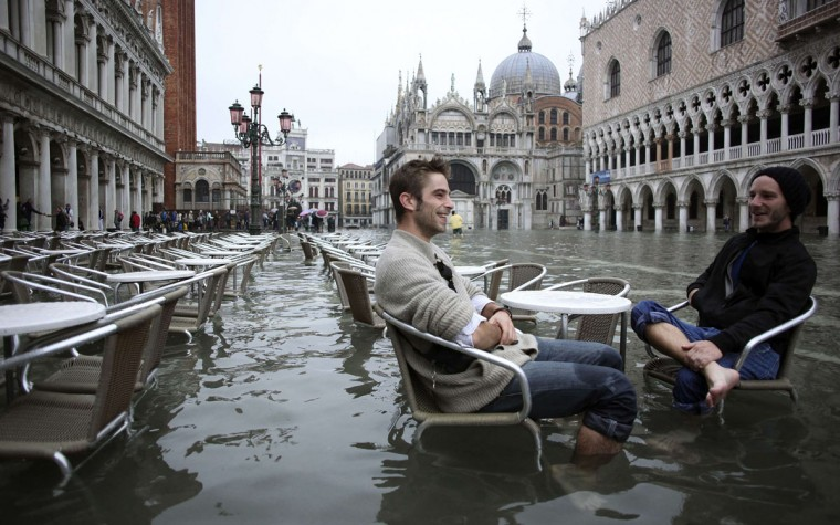 Tourists sit in St. Mark Square during a period of seasonal high water in Venice. The water in the canal city rose to 127 centimeters, or 50 inches, above the normal level. (Manuel Silvestri/Reuters)