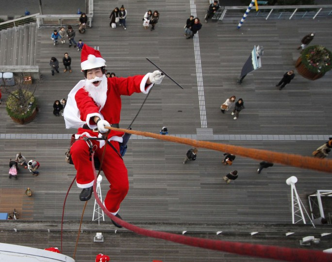 A window cleaner dressed as Santa Claus poses for photographers during an event to celebrate the upcoming Christmas holiday season at a shopping mall in Tokyo December 23, 2011. (Toru Hanai/Reuters)